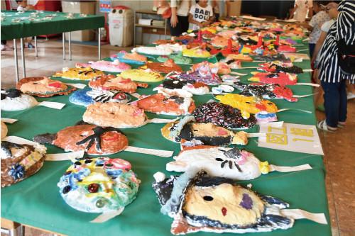 【図工教室】期間中に製作した作品を一同に展示。紙粘土でそれぞれ顔を作り 上げ、着色を施し、限られた時間の中で皆思うままに自分の作品を作り上げました。